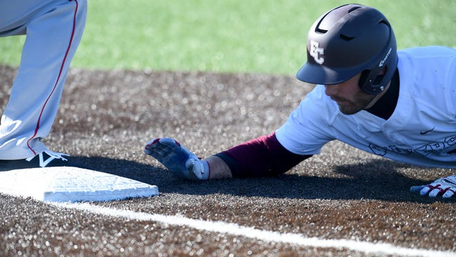 Earlham College's Danny Dopp dives back to first bast against Wittenberg University Wednesday, March 22, 2017 during a baseball game at Sadler Stadium in Richmond.