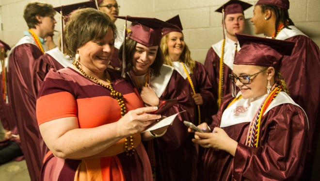 Grace Phelps, middle, and Skylar Onan, right, become  Facebook friends with their teacher Heather Spitzer, left, before the 2018 Henderson County High School Commencement at the Ford Center on Friday, May 18.
