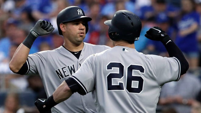 New York Yankees' Gary Sanchez, left, is congratulated by Tyler Austin (26) after his solo home run during the seventh inning of the team's baseball game against the Kansas City Royals at Kauffman Stadium in Kansas City, Mo., Saturday, May 19, 2018.