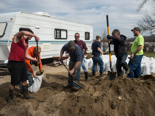 Kaleb Wittenbreaker, 5, second from right plays on a pile of sand as his family loads sand bags to protect his grandparents house in Point Twp. on Sunday, Feb. 25, 2018.