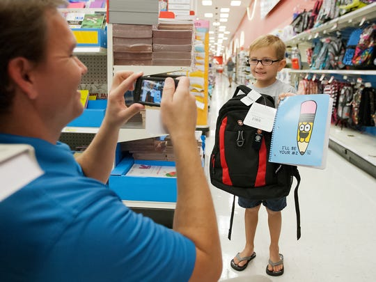 Michael Hill, left, takes a picture of his son, Caleb, 6, while back-to-school shopping at Target in Fort Myers during a previous tax-free holiday.