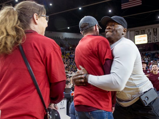 Doña Ana County Deputy Jamar Cotton, right, attempts to set the record for most hugs in a minute Saturday at the Pan American Center. Unofficially, Cotton embraced 112 people in 60 second to set the Guinness World Record.