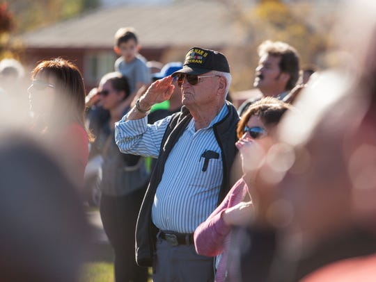 A veteran salutes the flag during a Veterans Day ceremony