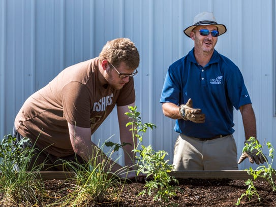 CJ Hamilton (left) finishes planting as Andy Rideout,