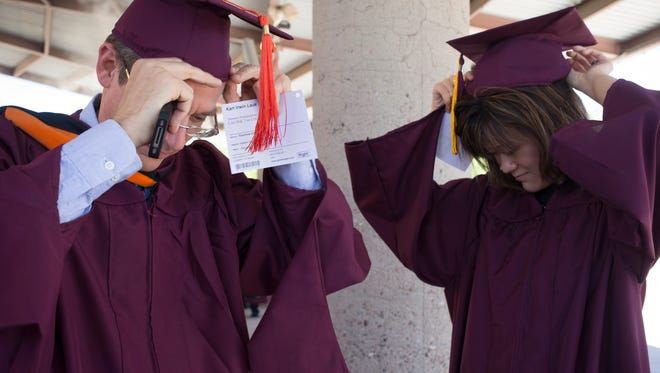 Karl Lauk (left) and his daughter, Stephanie Lauk, put on their caps in 2014 before graduating with degrees in electrical engineering from Arizona State University.