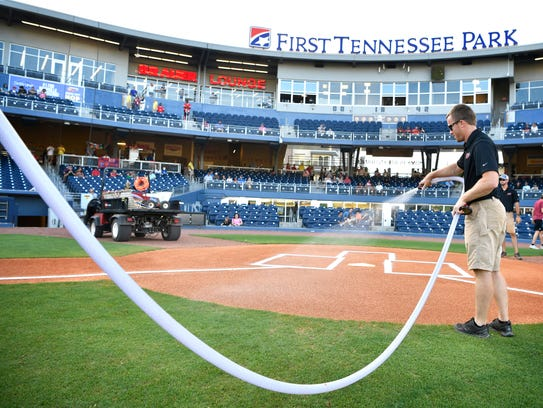 Head groundskeeper Thomas Trotter waters down the dirt