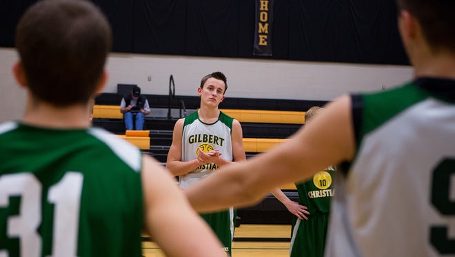 Mitchell Lightfoot, (middle) a senior at Gilbert Christian High School, practices in the school gym with the basketball team December 3, 2014 in Gilbert.