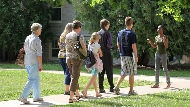 A Lawrence University student leads a tour of the campus for a visiting prospective student and his family.