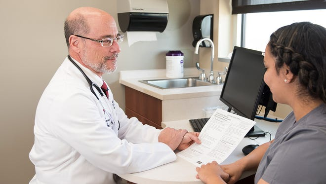 Peter Catinella, M.D., M.P.H., reviews information about the flu with a patient.