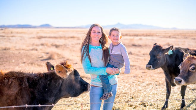Ashley White and her son Preston stand around the cows that give the raw milk on their farm in Hurley.