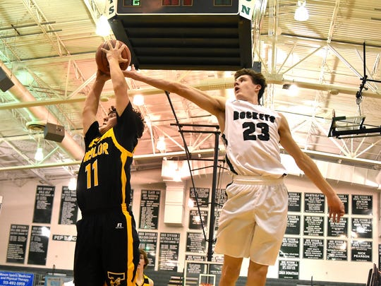 Evan Brunot (23) can't quite stretch far enough for McNicholas as Taylor's Bennett Welherer (11) pulls down a rebound for the Yellow Jackets, Feb. 23, 2018.