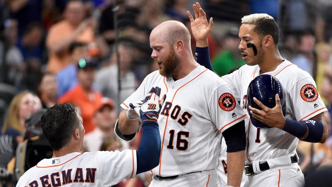 Houston Astros' Brian McCann (16) celebrates his solo home run off Seattle Mariners starting pitcher Hisashi Iwakuma with Alex Bregman (2) and Carlos Correa, right, during the third inning of a baseball game, Tuesday.