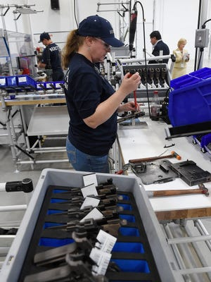 Sally Ward assembles firearms after watching the festivities at the official opening of the new BERETTA U.S.A. Corp state-of-the-art manufacturing facility.