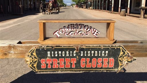 A sign marks a street closed in Tombstone on Monday, Oct. 19, 2015, after an actor staging a historical gunfight in the Old West town was shot with a live round during a show that was supposed to use blanks.