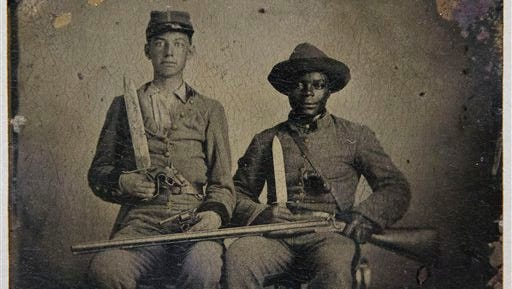 This handout photo provided by the Library of Congress shows Sgt. Andrew Martin Chandler of the 44th Mississippi Regiment, left, and Silas Chandler posing in this tintype, circa 1861. An enigmatic Civil War photo of a white man and a black slave, both in Confederate uniforms, has been donated to the Library of Congress. The Washington Post reports that the tintype image made in 1861 was donated by collector Tom Liljenquist of McLean, Va., who bought it from descendants of the white soldier.