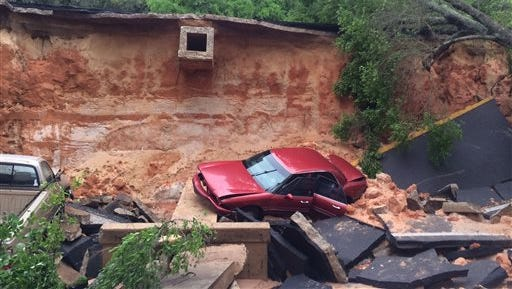 In this image provided by Brantly S. Keiek shows several vehicles that collapsed together with a portion of the Scenic Highway in Pensacola, Fla., Thursday, April 30, 2014. Heavy rains and flooding have left people stranded in houses and cars in the Florida Panhandle and along the Alabama coast. According to the National Weather Service, an estimated 15-20 inches of rain has fallen in Pensacola in the past 24 hours. (AP Photo/Brantly S. Keiek)