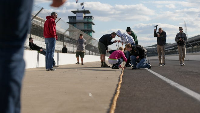 Scouts, volunteers and their families lay out a 450-foot popcorn string for measurement in pit lane at IMS.