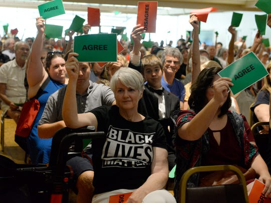 People hold up signs during a town hall meeting held