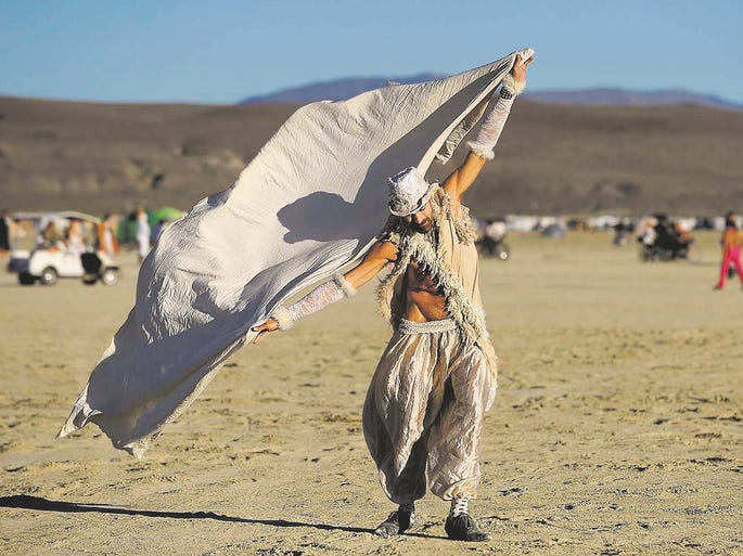 Jeffery Bale of Portland, Ore., uses a scarf to play with the wind on the playa on Thursday morning at Burning Man on Sept 2, 2010.
