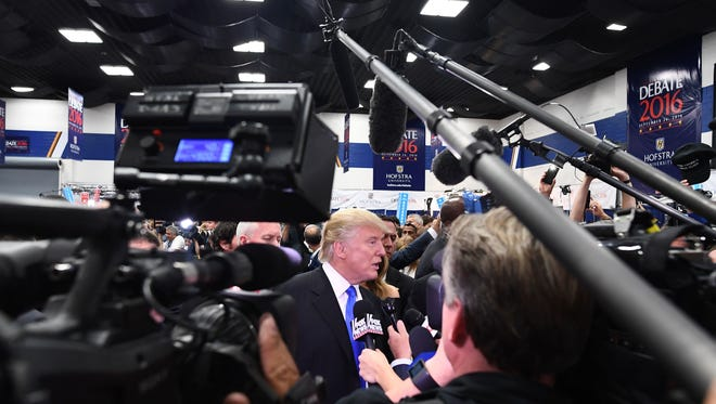 """Republican nominee Donald Trump (C) speaks with reporters in the """"Spin Room"""" after the first presidential debate at Hofstra University in Hempstead, New York on September 26, 2016. / AFP / Jewel SAMAD        (Photo credit should read JEWEL SAMAD/AFP/Getty Images)"""