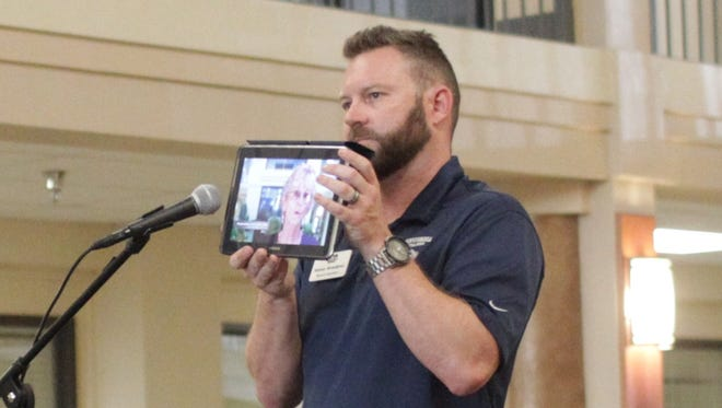 Kenny Breedlove, owner of Shameless O'Leery's Irish Pub in downtown Redding, holds up an iPad through which Margaret Beck addressed the audience on Tuesday.
