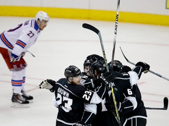 Members of the Los Angeles Kings celebrate Marian Gaborik's goal as New York Rangers defenseman Ryan McDonagh skates by the during the third period of Game 2 in the NHL hockey Stanley Cup Finals in Los Angeles, Saturday, June 7, 2014. (AP Photo/Jae C. Hong)