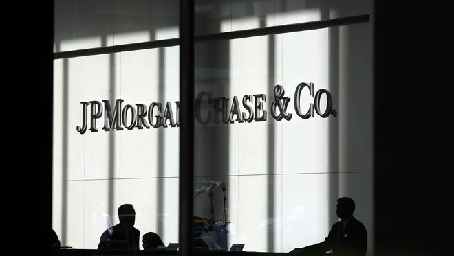 People pass a sign for JPMorgan Chase & Co. at its headquarters in Manhattan.