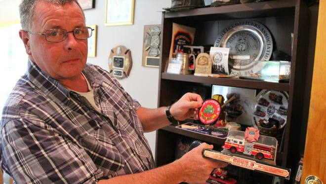 John Leonard of Nanuet, a retired New York fire department lieutenant, holds some of the collectibles displayed at his home on Sept. 20, 2013.