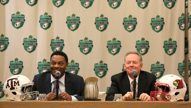 Texas A&M coach Kevin Sumlin and Louisville coach Bobby Petrino smile while taking questions from the media Tuesday afternoon before the Franklin American Mortgage Music City Bowl in Nashville.
