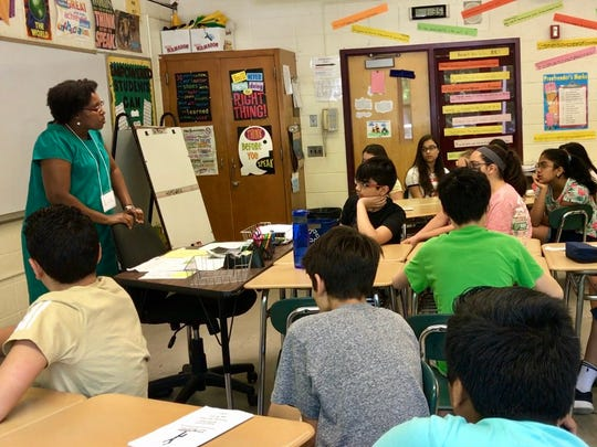 Eugenie Mukeshimana of Rwanda addresses students at Robert R. Lazar Middle School in Montville on May 18 along with 49 other survivors of atrocities around the world.