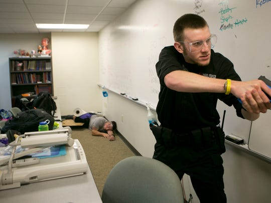Criminal justice student Andrew Henke clears a room