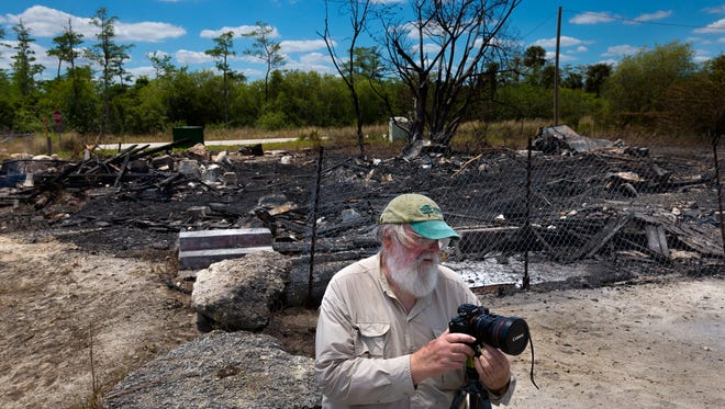 Acclaimed Everglades photographer Clyde Butcher sets up to photograph the smoldering ruins of the historic Monroe Station on Sunday, April 10, 2016, in Ochopee, Fla. A fire destroyed the historic way station on the Tamiami Trail between Naples and Miami. It was one of a series of way stations built in the late 1920s after the opening of the Tamiami Trail to help travelers.