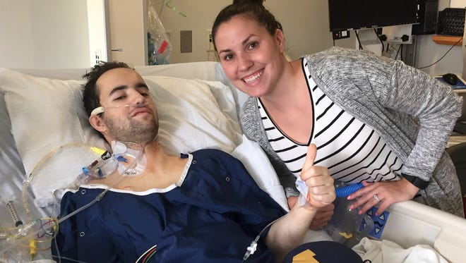 Chris Newton gives the thumbs-up sign with life partner Jessica Matthews at his bedside. Both are 2008 graduates of Farmington High School. The former Farmington High School goalie and assistant hockey coach received new lungs and a new lease on life when he had a double transplant this summer.