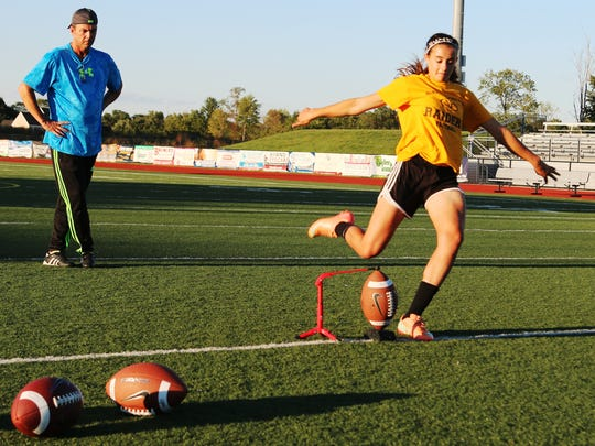 As former NFL kicker Pete Stoyanovich watches, Lynn Lerner practices her kick.
