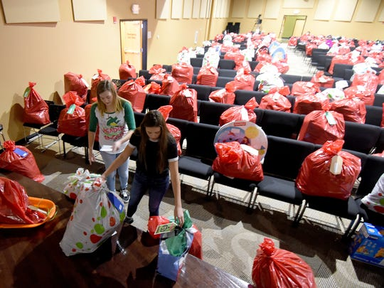 Lizzie Burson and Riley Kinney, both 15 years old, gather Christmas gifts for a family on Wednesday at the Crossroads Community Church.