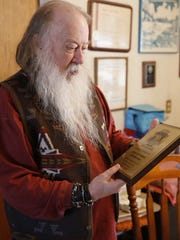 """Sherwood """"Woody"""" Moore examines the plaque he received after being inducted into the South Dakota Rock and Roll Association's Hall of Fame."""