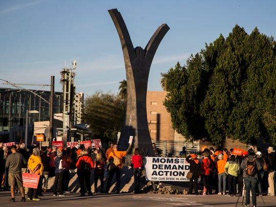 People arrive during a vigil to end gun violence after