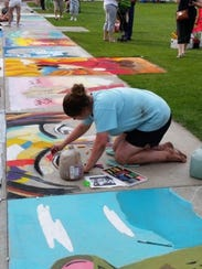 Paige Bootz works on a portrait at Chalkfest 2015 in