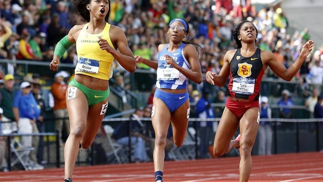 Oregon's Ariana Washington (from left), looks to the video board after winning the women's 100-meter dash in front of Kentucky's Kianna Gray and USC's Tynia Gaither at the NCAA outdoor track and field championships in Eugene on Saturday.