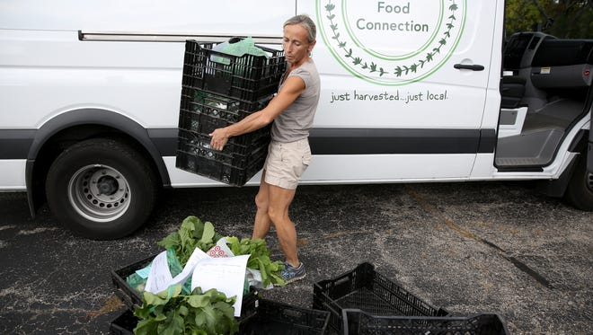 Alice Chalmers carries fresh vegetables to her van at the Madeira Winter Farm Market.