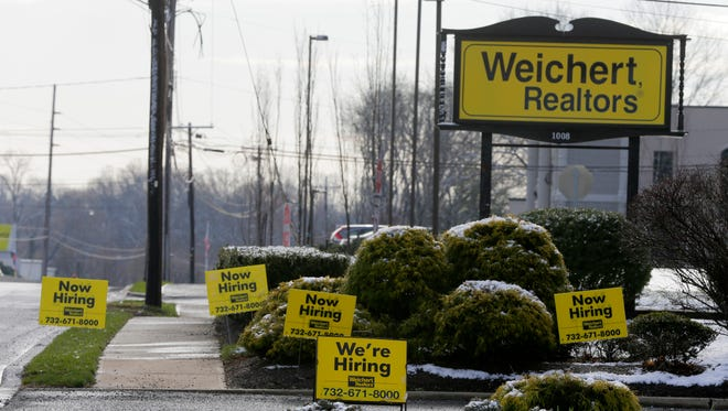"Weichert Realtors displays ""We're Hiring"" signs outside its office building on Route 35 South in Middletown."