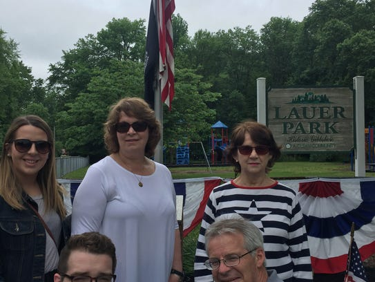 "Family members of Vietnam War casualty Joseph E. ""Jay"" Lauer gather under his funeral flag on Memorial Day at a Gibbsboro playground named for the Marine. He was killed on Memorial Day weekend 50 years ago and his flag flies only on Memorial Day each year. Pictured are great-niece Laura Naylor, niece Karen Naylor and Mary Huber, Lauer's sister; great-nephew Sean Naylor, bottom left, and Tim Naylor."