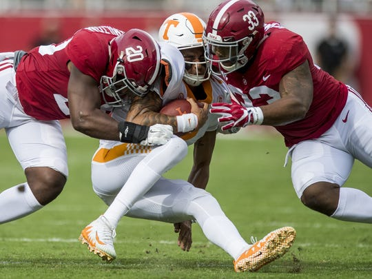 Alabama linebacker Shaun Hamilton (20) and linebacker Anfernee Jennings tackle Tennessee quarterback Jarrett Guarantano last year.