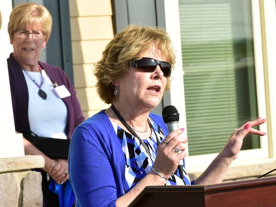 Barbara Channing, executive director, invites visitors to tour Women In Need at Progress Road, Chambersburg, during a grand opening and ribbon cutting.