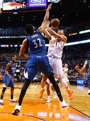 Phoenix Suns guard Devin Booker (1) drives to the basket against Minnesota Timberwolves center Karl-Anthony Towns (32) in the second half at Talking Stick Resort Arena on March 14, 2016.