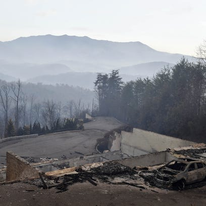 A burned-out car rests outside a destroyed home Nov.