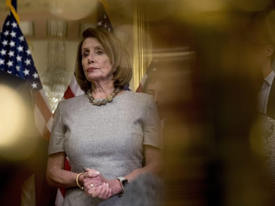 House Speaker Nancy Pelosi of Calif., accompanied by House Democratic members, listens to a reporters question after signing a deal to reopen the government on Capitol Hill in Washington, Friday, Jan. 25, 2019. (AP Photo/Andrew Harnik)