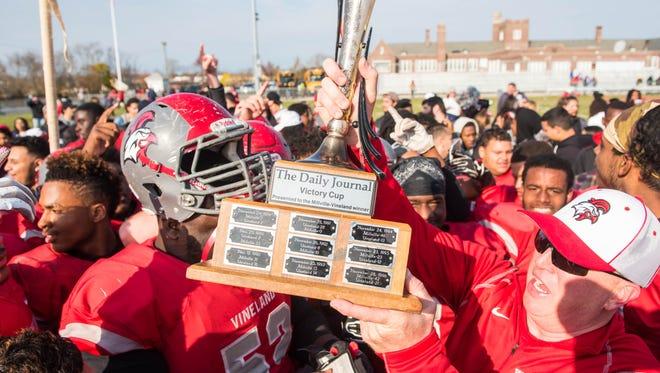 Vineland head coach Dan Russo celebrates a 45-28 win against Millville with The Daily Journal Victory Cup at Gittone Memorial Stadium on Thursday, November 24.