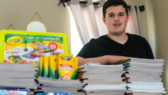 Carter Crockett, 15, poses for a photo with coloring books and crayons collected to be donated to St. Jude Childen's Research Hospital in Memphis at his home in Millville on Monday, June 26.
