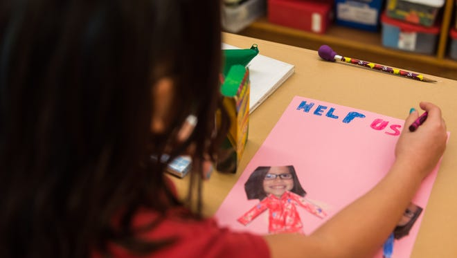 D'Ippolito third grader Demi Rodriguez decorates a poster for a pajama drive for underpriviledged children at D'Ippolito Elementary School on Monday, November 13.